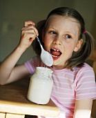 Mädchen schleckt Löffel ab beim Joghurt Essen