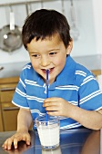 Small boy drinking milk through a straw