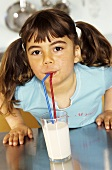 Small girl drinking a glass of milk through two straws