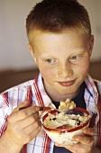 Schoolboy eating fruit muesli