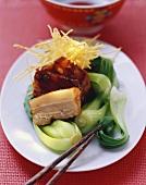 Glazed belly pork with pak choi and straw potatoes