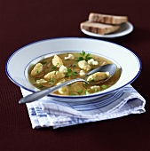 Semolina dumpling soup with vegetables and parsley