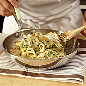 Mixing ribbon pasta with goat's cheese and peas