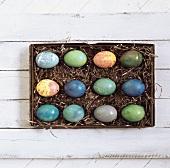 Karton mit gefärbten Ostereiern