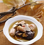 Broth with pieces of pig's tail, yam and mushrooms