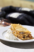 A piece of apple strudel with whipped cream