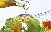 Olive oil running over spoon onto salad