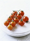 Several cherry tomatoes on a stone slab