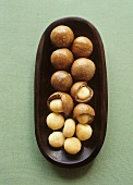 Macadamia nuts, shelled and unshelled in a bowl