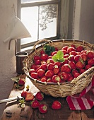 A basket of strawberries in front of a window