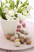 Sweet Easter eggs on a plate with bunch of spring snowflakes