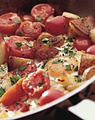 Pan-cooked tomatoes and potatoes with fried egg