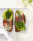 Grilled bread topped with asparagus and bacon salad