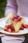 A piece of orange cake with fresh strawberries