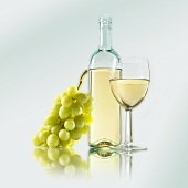 Glass of white wine, white wine bottle and grapes