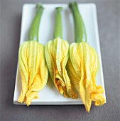 Three courgette flowers on a platter