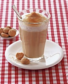A glass of milky coffee with amaretti