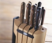 A wooden knife block with various kitchen knives