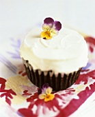 Chocolate muffin with icing and pansies