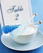 Two blue candy sticks on a cup of cappuccino