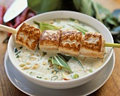 Thai soup with fried skewered salmon