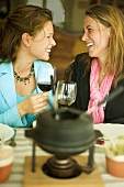 Two women clinking wine glasses at fondue meal