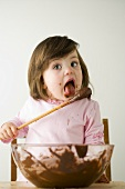 Small girl licking wooden spoon