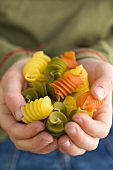 Coloured pasta in child's hands