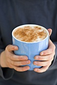 Child's hands holding a cup of hot chocolate