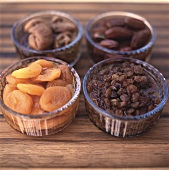 Four different dried fruits in small glass bowls