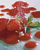 Strawberry with flower and leaf lying in strawberry sauce