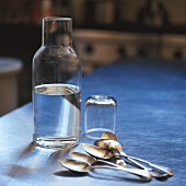 A bottle of water with glass and spoons