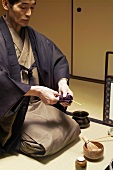 Tea master at tea ceremony, cleaning spoon