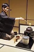 Tea master at tea ceremony, pouring water into kettle