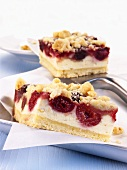 Two pieces of cherry cheesecake with crumble topping