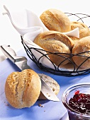Bread rolls in bread basket and jam