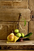 Apples and a pear in front of a wooden door