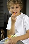 Boy eating vegetable sticks