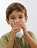 Kleiner Junge trinkt ein Glas Milch