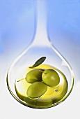 Ein Löffel mit Olivenöl und drei Oliven