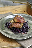 Roast partridge breasts wrapped in bacon on red cabbage