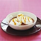 Poached meringues with caramel sauce on chocolate pudding