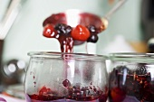 Ladling berry jam into jar