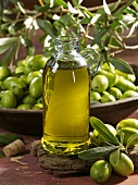 A bottle of olive oil with fresh olives