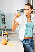 Woman holding a glass of orange juice in her hand