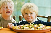Two boys, nachos with tomato salsa and guacamole