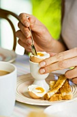 Eating a boiled egg and soldiers (strips of toast)