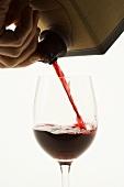 Rotwein aus dem Karton in ein Glas gießen