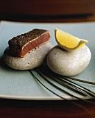 Seasoned tuna with lemon wedge