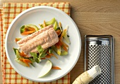 Cooked salmon on a bed of vegetables